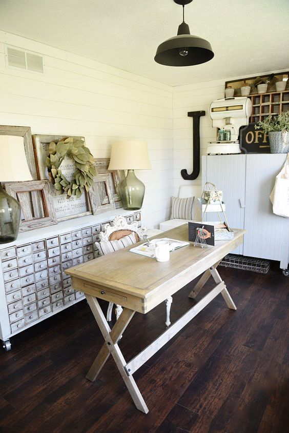 an inspiring home office with white beadboard walls, a wooden desk, a shabby chic storage unit, a black lamp and some decor