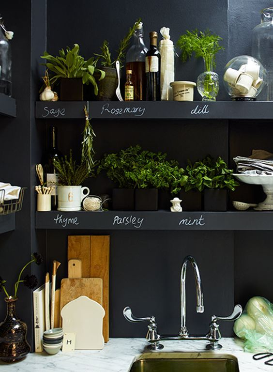 chalkboard walls with built-in open shelves over the whole kitchen are great for any kinds of marks, messages and other stuff
