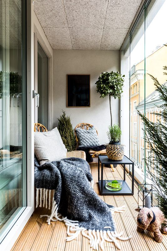a Nordic balcony with rattan furniture, printed textiles, potted plants and candle lanterns for a chic space