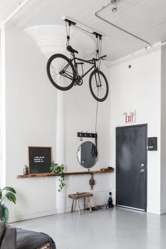 a Scandinavian space with a bike holder attached to the ceiling allows to store it in a creative and comfortable way and make it part of decor