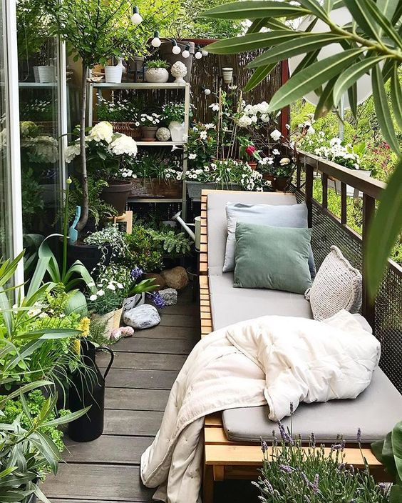 a balcony garden with potted greenery and blooms and a wooden lounger with upholstery and pillows is a gorgeous place to be