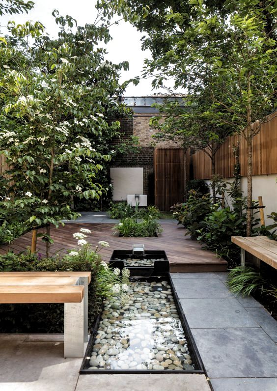 a beautiful summer terrace with trees, blooms and greenery, a fountain with pebbles, a bench and a deck