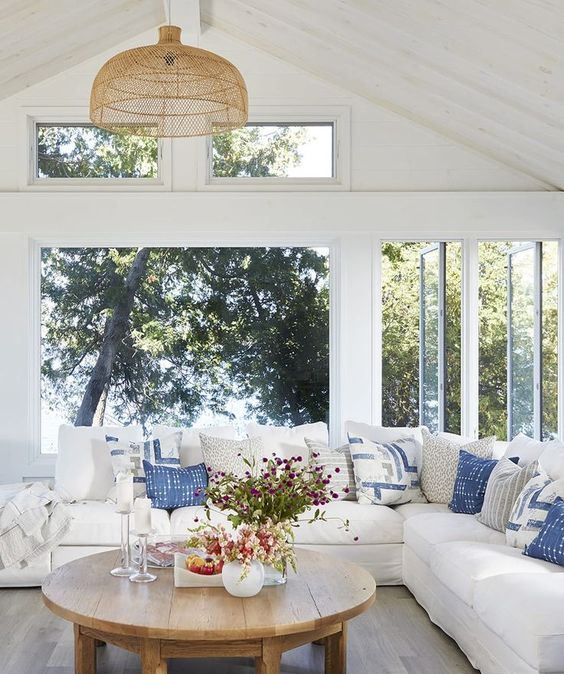 a beuatiful modern farmhouse coastal sunroom with a large sectional, blue pillows, a wooden table and woven chandelier