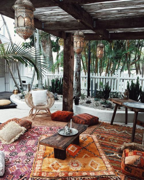 a boho terrace with colorful layered rugs, bright cushions and pillows, a rattan chair, Moroccan lanterns and cacti all around