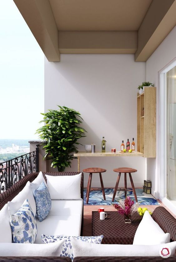 a bold balcony with dark wicker furniture, a small Murphy bar and stools plus a statement plant in the corner