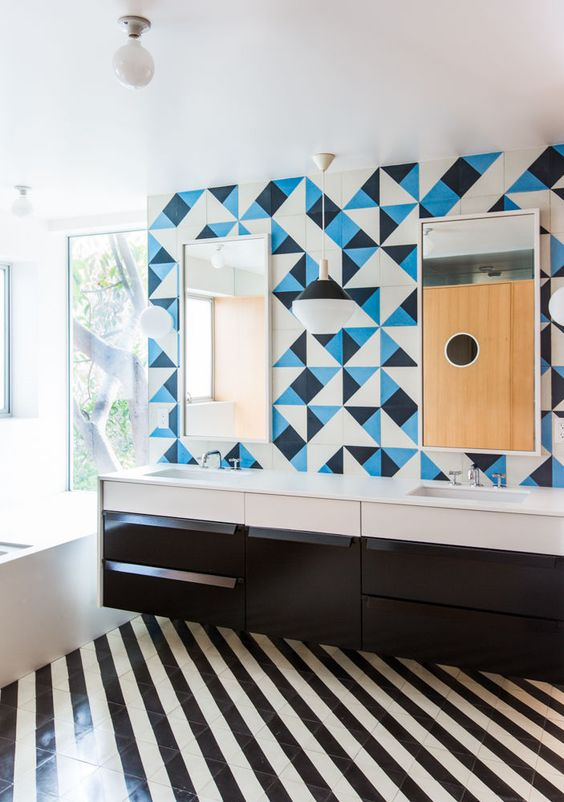 a bold bathroom with a striped black and white tile floor, a black vanity, white appliances, a blue, black and white tile wall