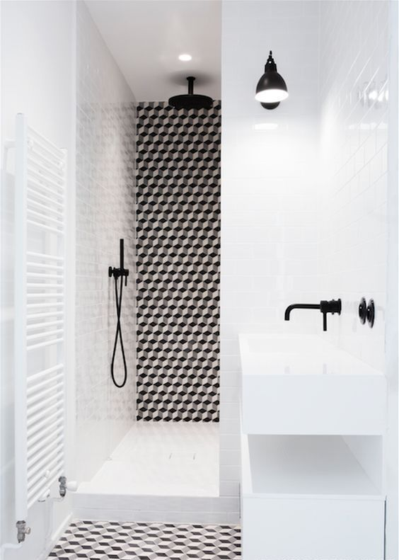 a bold black and white bathroom with geo tiles and black fixtures looks ultra-modern and very chic
