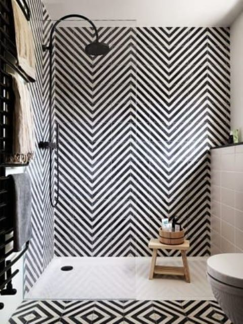 a bold black and white bathroom with herringbone patterned tiles and geometric ones on the floor plus black fixtures