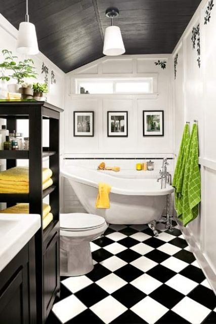 a bold vintage bathroom with a black slanted ceiling, a black and white tile floor, black cabinets and a clawfoot tub plus bold textiles