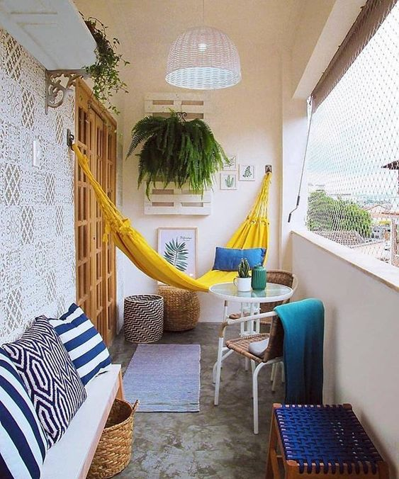 a bright and cheerful summer balcony in yellow and blue, with printed and just bright textiles, a yellow hammock and some greenery