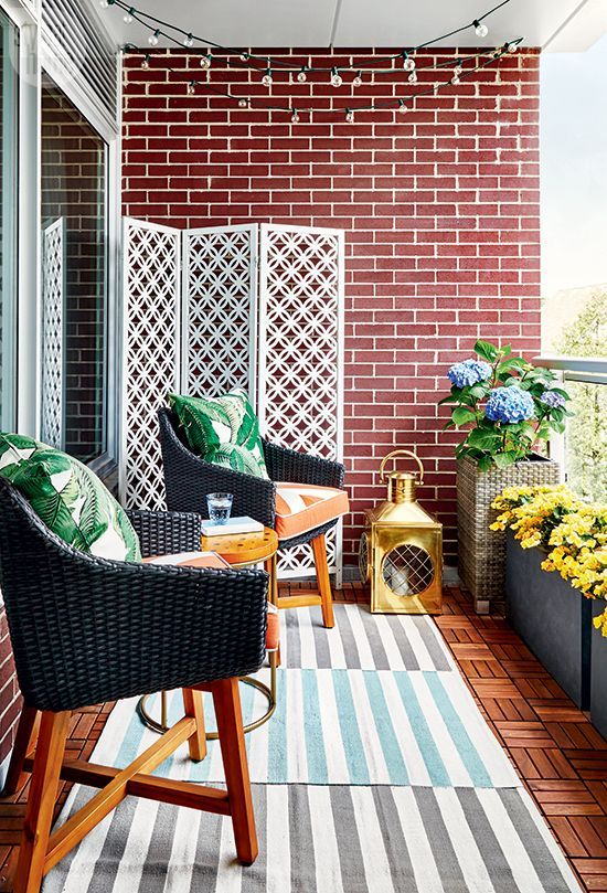a bright and stylish balcony with layered rugs, wicker chairs and printed pillows, potted blooms and a large candle lantern