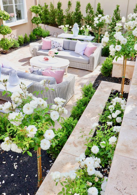 a bright and vivacious summer terrace done with tiles, white wicker furniture, pastel upholstery and pillows and lots of greenery and blooms