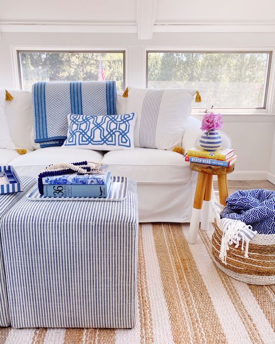 a bright modern sunroom with white and striped furniture, printed pillows and a jute rug is very cool
