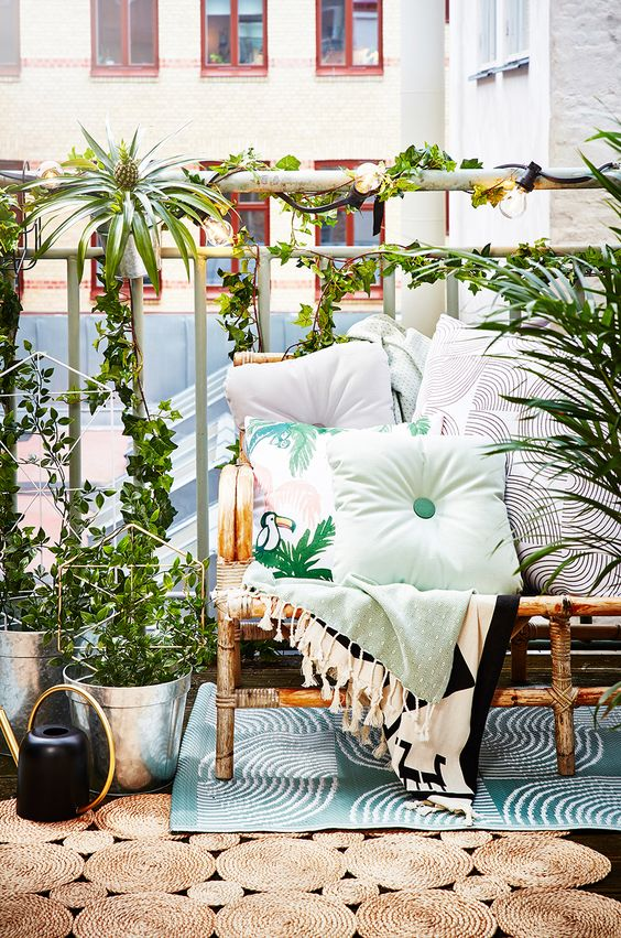 a bright summer balcony with a rattan sofa, printed textiles, potted greenery and layered rugs feels very tropical-like