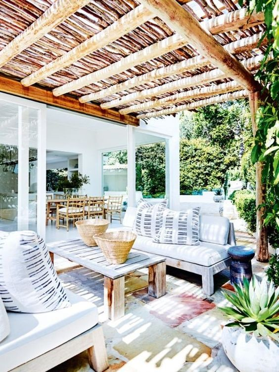 a bright summer terrace with wooden furniture, watercolor rugs and striped pillows feels very island-like