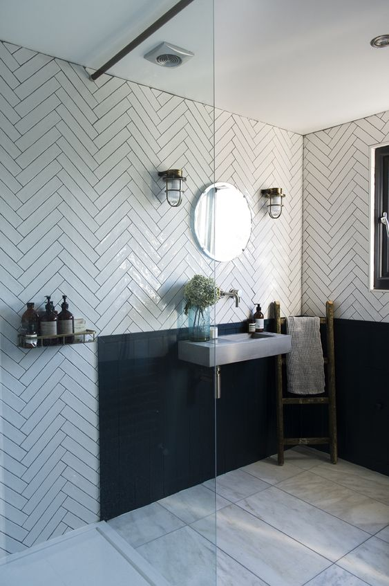 a catchy and chic bathroom with white herringbone tiles, a black backsplash, a concrete wall-mounted sink and vintage lamps