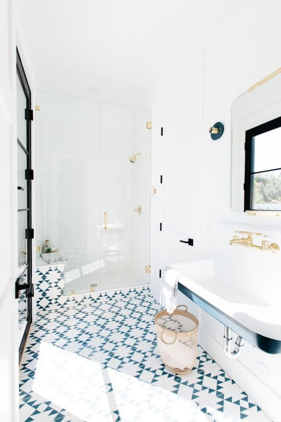 a catchy bathroom with a blue and white tile floor, a wall-mounted sink, black and gold fixtures and touches