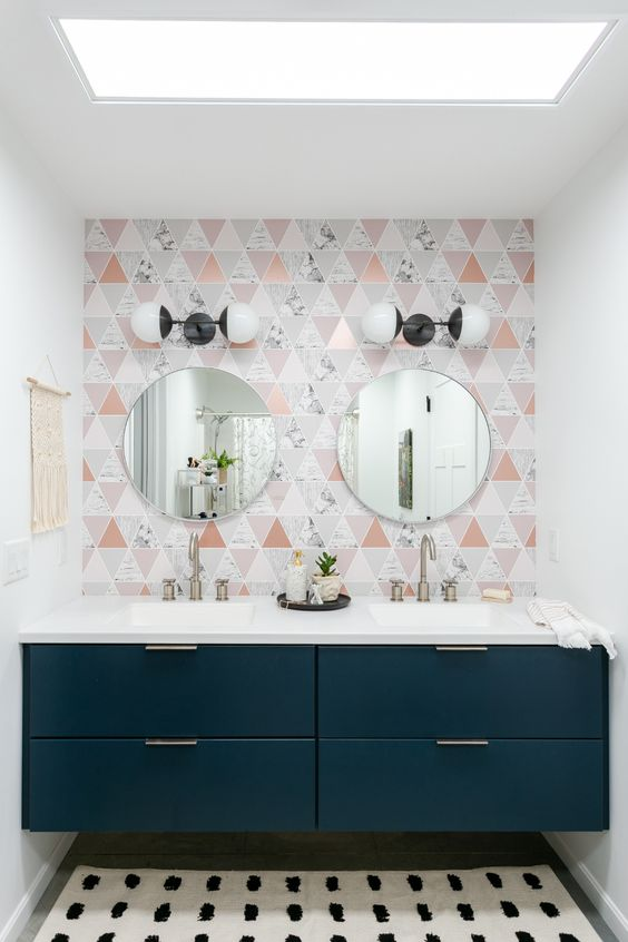 a catchy bathroom with a geo tile wall, a navy built-in vanity and round mirrors plus vintage wall sconces