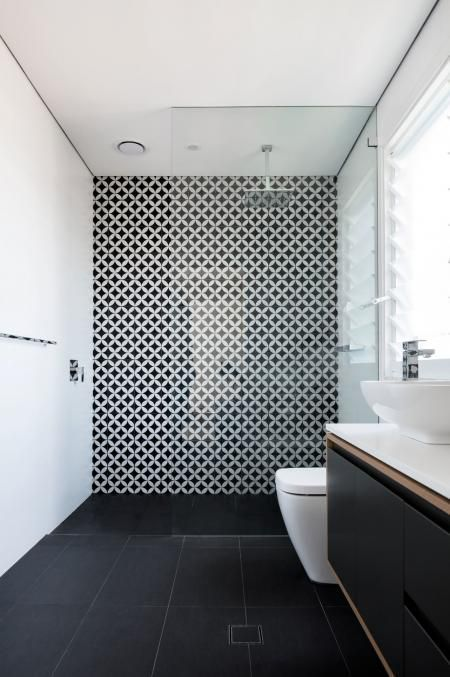 a chic and contrasting bathroom with white walls and a black tiel floor, a catchy geometric wall in the shower space and a black vanity