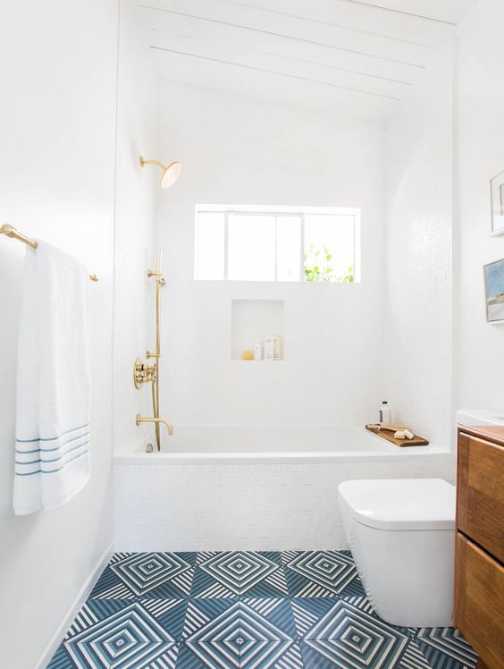a chic bathroom in white, with a blue geo tile floor, a wooden vanity, gold fixtures is a serene and airy space