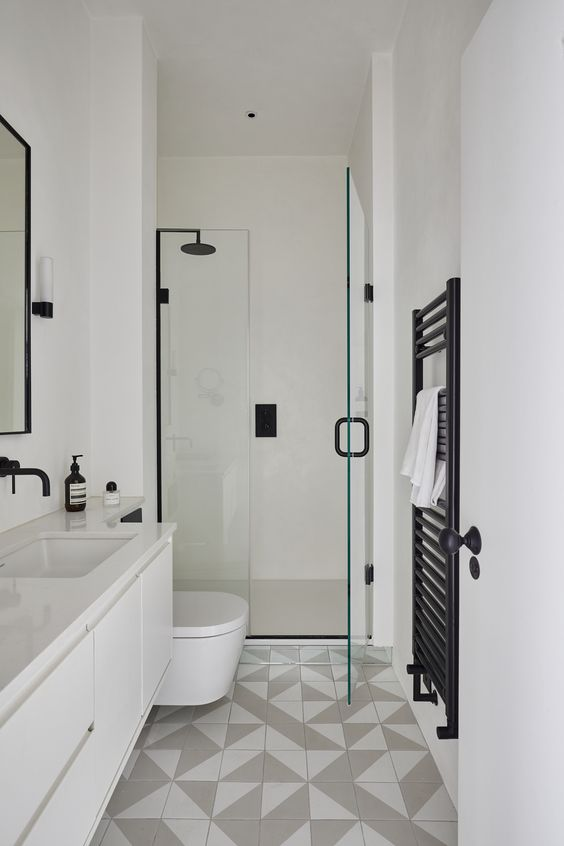 a chic contemporary bathroom with grey and white geo tiles on the floor, white furniture and appliances and black fixtures
