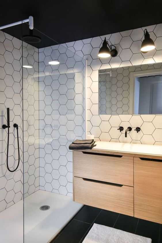 a chic modern bathroom with white hex tiles on the walls, black tiles on the floor and a floating wooden vanity plus black fixtures