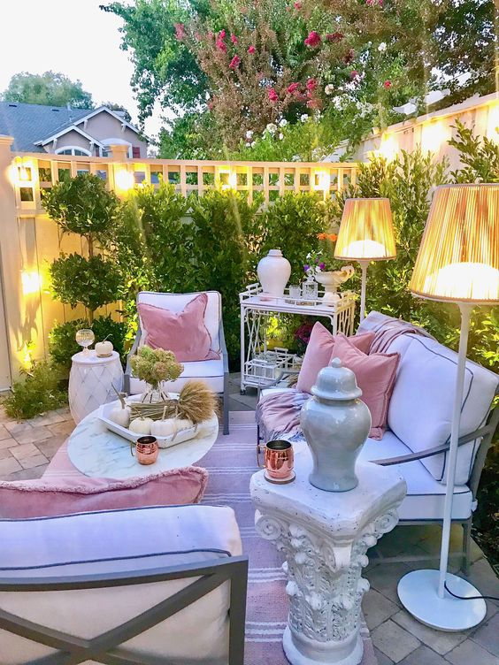 a chic pastel terrace with white contemporary furniture, floor lamps, refined tables and a greenery wall