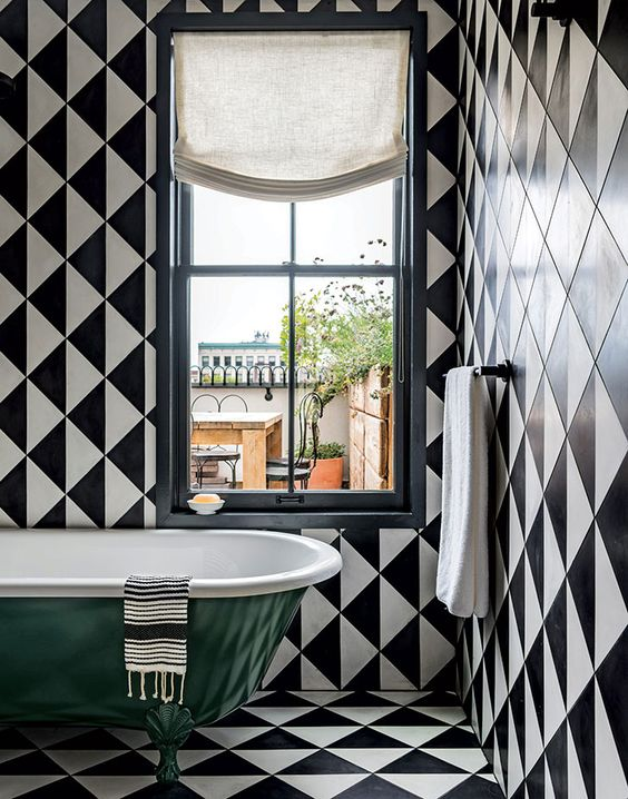 a chic retro bathroom with black and white tiles everywhere and a bold green clawfoot tub plus white textiles