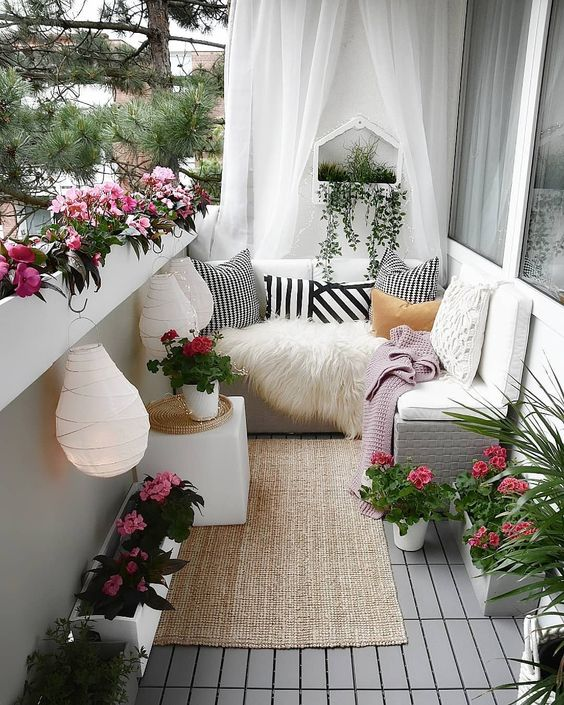 a chic yet small summer balcony in white, with sheer curtains, a jute rug, potted blooms, paper lanterns and printed textiles