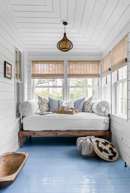 a coastal sunroom with a daybed squeezed in, printed pillows and a basket and a dough bowl