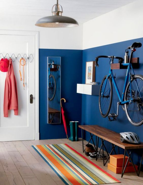 a colorful entryway with a bold blue wall, a holder for the bike, a bench and some hooks and hangers for various stuff is ultimate