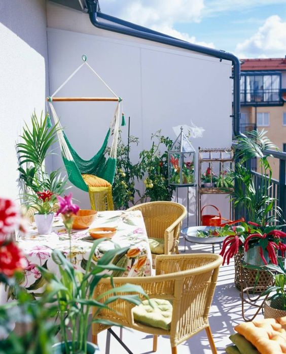 a colorful summer balcony with yellow chairs, printed textiles, a green hammock chair and lots of potted greenery and blooms