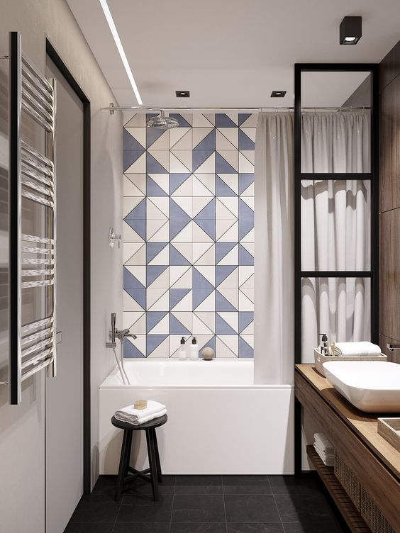 a contemporary bathroom with a blue geo tile wall in the bathtub space, black fixtures, a wooden vanity and white appliances