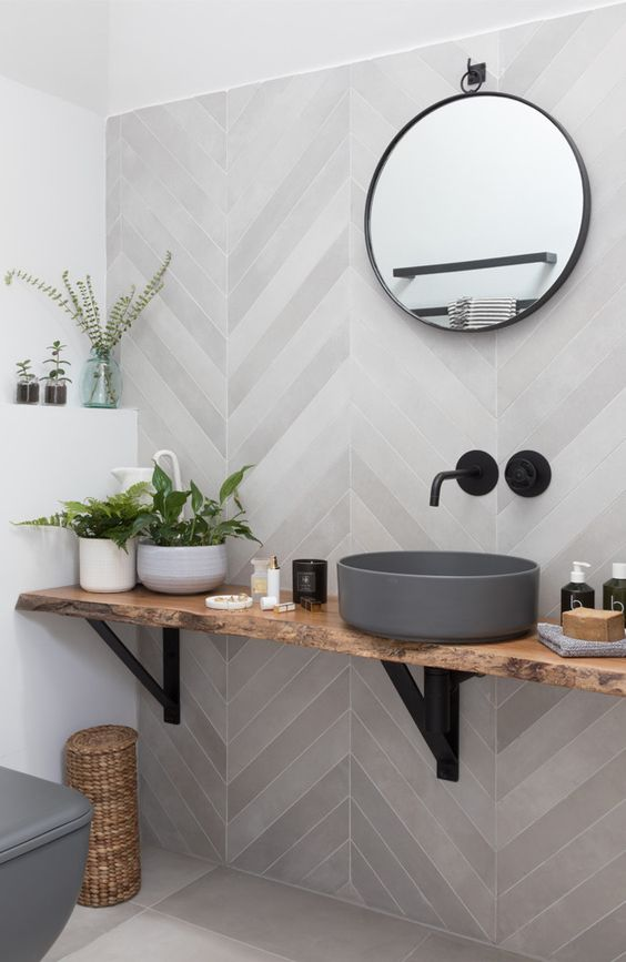 a contemporary bathroom with grey herringbone tiles, a wall-mounted vanity and a concrete sink plus a round mirror