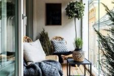 a contemporary sunroom with a boho feel – a couple of wicker loungers, a table, a lantern and potted greenery