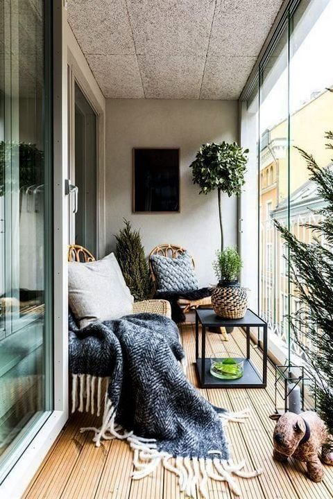 a contemporary sunroom with a boho feel - a couple of wicker loungers, a table, a lantern and potted greenery