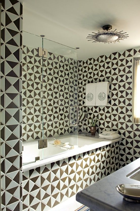 a contrasting bathroom clad with black and white geo tiles, shiny metallic fixtures and touches is veyr eye-catchy and very bold