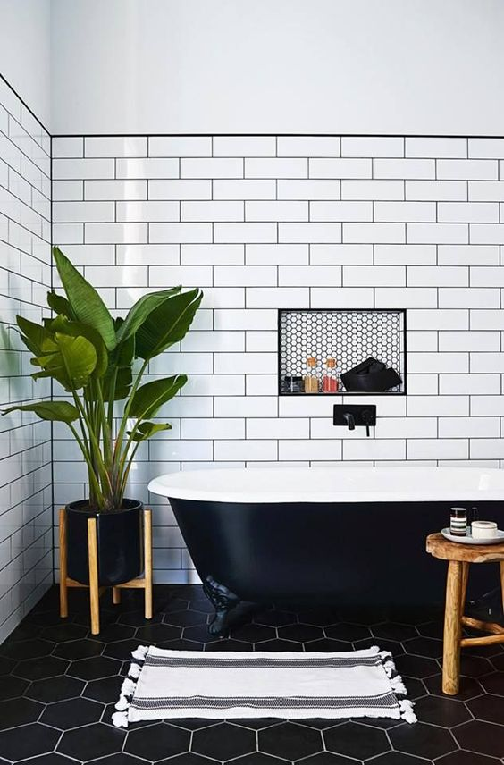 a contrasting bathroom with white subway tiles and black hex ones, a black clawfoot tub and wooden furniture