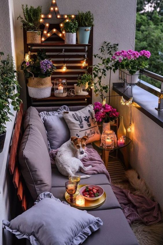 a cozy small balcony with a pallet wall and sofa, some potted blooms and greenery and candle lanterns