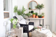a cozy small sunroom with boho touches, a jute rug and ottoman, wooden chairs and lots of potted greenery and lanterns