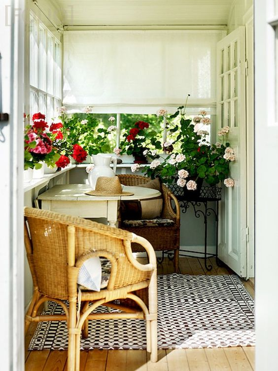 a cozy small sunroom with wicker chairs and a foldable table, with lots of blooms in pots and Roman shades