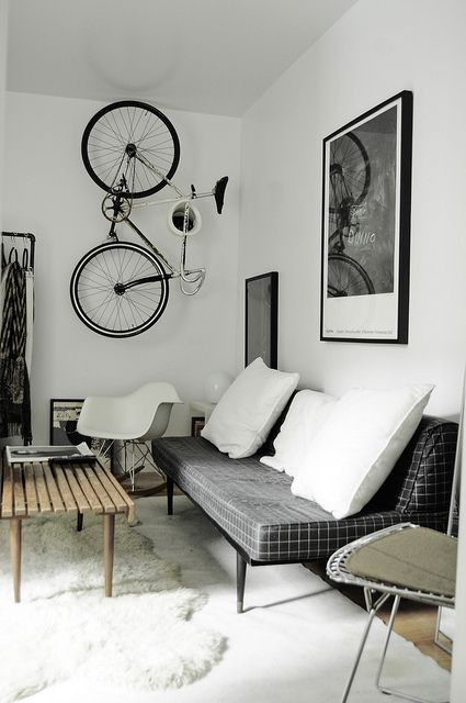 a creative bike holder on the wall that allows storign it vertically is a lovely idea for a Scandinavian space