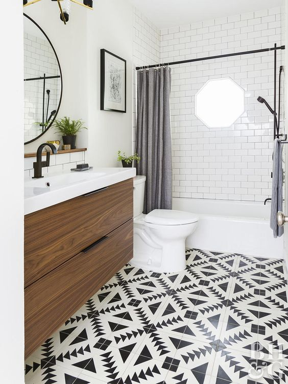 a farmhouse bathroom with a black and white tile floor, grey curtains, a floating vanity and black fixtures for a modern feel
