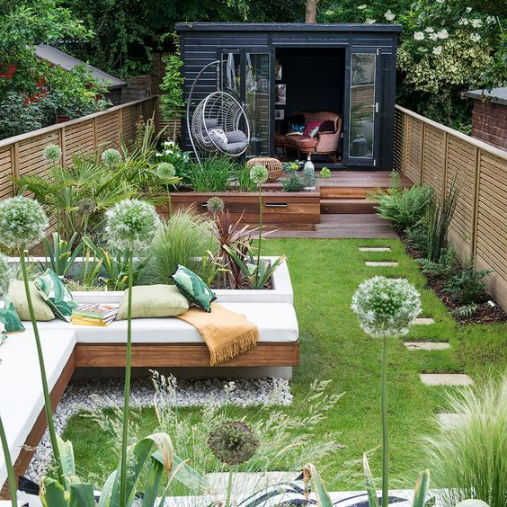 a fresh and welcoming summer terrace with a deck, a built-in bench, a lawn and some greenery and other plants
