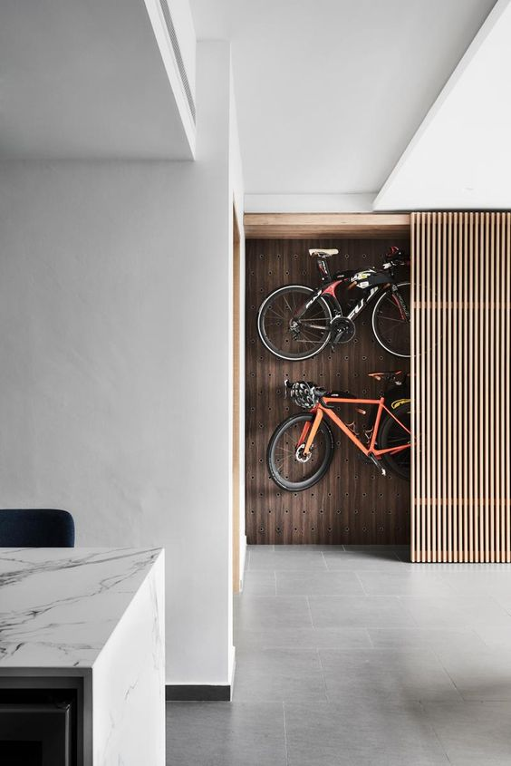 a hidden storage space with a pegboard wall and bikes attached to it and a sliding wood slab door allows hiding all your stuff