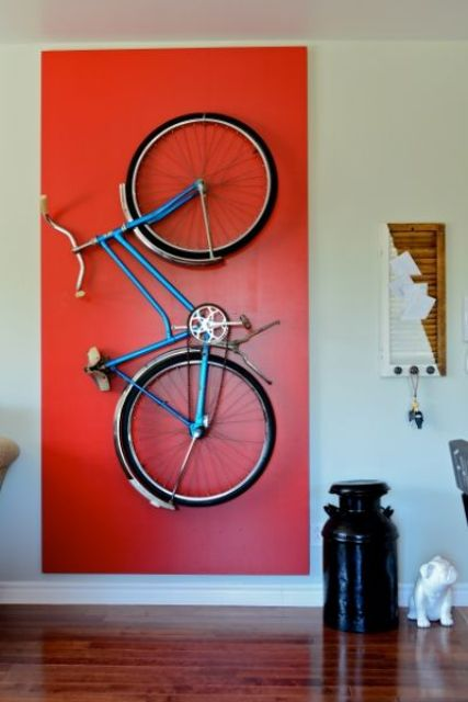 a holder for storing the bike on the wall and a bold red accent to highlight it is a very cool idea to accent what you really like