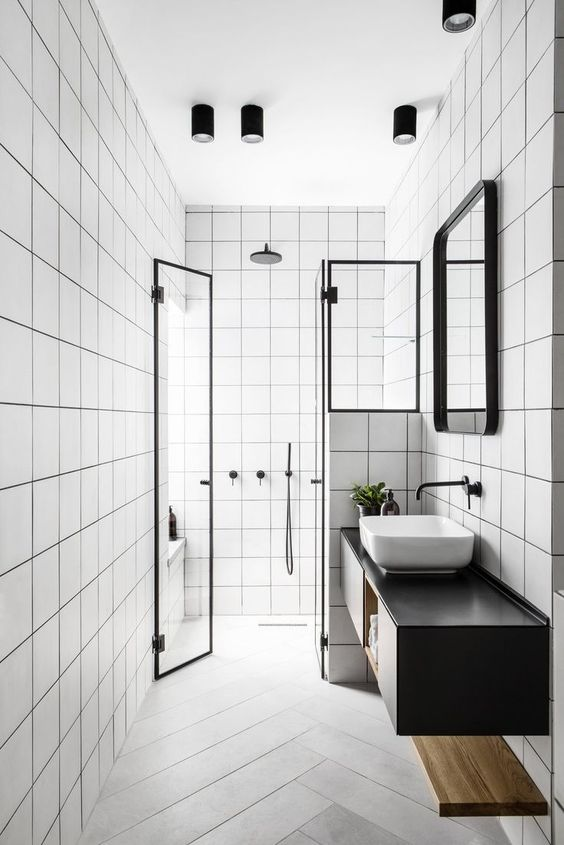a laconic black and white bathroom with square white tiles and herringbone tiles on the floor, a black floating vanity and black fixtures