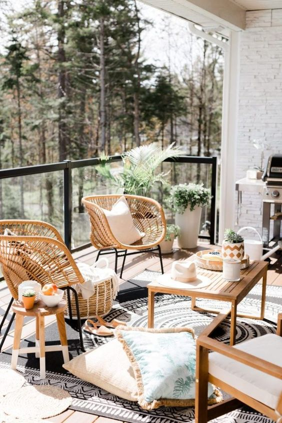 a large and welcoming balcony with wooden and wicker furniture, potted plants, a grill and some cozy textiles