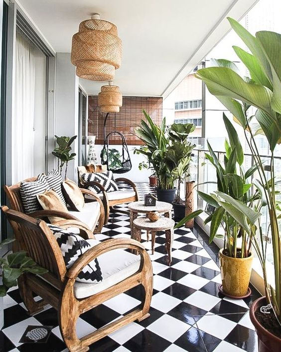 a large balcony with black and white tiles, wooden furniture, wicker lamps and printed pillows and lots of plants