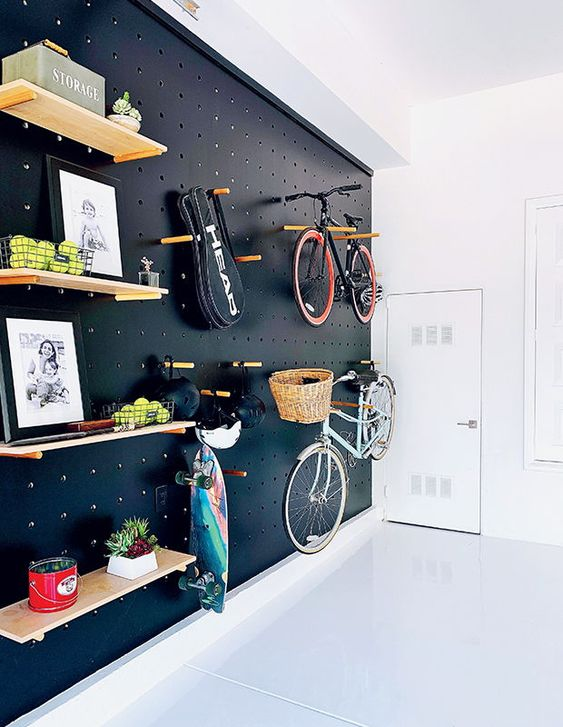 a light-filled entryway with a black pegboard wall with lots of shelves, hangers, hooks and with bike holders is a gorgeous idea for a contemporary space